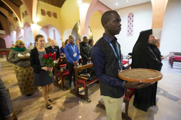 "LWF delegates Pascal Kama, 31, General Secretary of the Lutheran Church Of Senegal (right), and Caroline Bader, 31, LWF Youth Secretary (left), hold earth and flowers, respectively, in the opening procession of an ecumenical worship service of ""Prayer for the Planet"" at the Roman Catholic Church of the Holy Martyrs in Marrakech during the COP22 UN climate conference in Morocco, 8 November 2016."