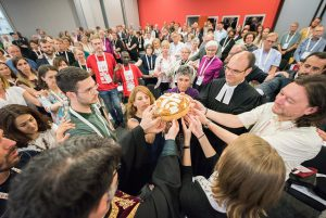 People gather around a loaf of bread as part of the closing service of the Novi Sad General Assembly